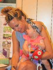 Stacy Peterson holds her daughter Eva, 6 months, during the Fourth Trimester Club.