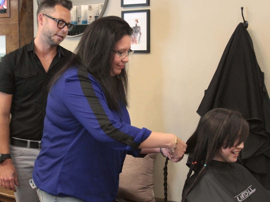 Above, Mara Romo cuts the first braid of her daughter, Mia Bella's hair, as stylist Blake Mason of Rain the Salon looks on.