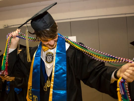 Ben Blaylock has some many honor cords he has trouble keeping them untangled. He and other graduating seniors of Central Magnet School prepare for the ceremonies at MTSU.