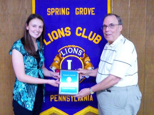 """Scholarship Chairman Terry Lehr presents a plaque along with a 1000 scholarship to Danielle Paterson. The scholarship is awarded to the area high school senior who submits the best essay describing how they will use their studies to advance the goals of """"Lionism."""" Paterson is a 2015 graduate of Spring Grove High School and is a member of the National Honor Society, the International Thespian Society and the Tri-M Music Honor Society. She plans to attend Messiah College this fall where she will major in occupational therapy."""