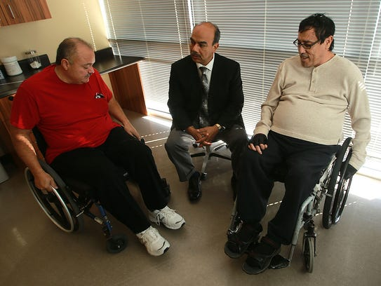 Dr. Hector Pacheco, center,  visited with patients
