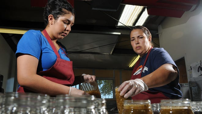 Nohemy Sotelo, left, and Ivonne Sotelo, workers at Ol' Gringo Chile Company, fill jars of salsa at the plant.