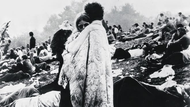 In this August 1969 file photo, a couple hugs during the Woodstock Music and Art Festival in Bethel, N.Y.