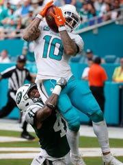 Miami Dolphins wide receiver Kenny Stills (10) catches a touchdown pass over New York Jets cornerback Buster Skrine (41), during the second half of an NFL football game, Sunday, Oct. 22, 2017, in Miami Gardens, Fla. (AP Photo/Wilfredo Lee)