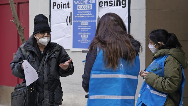 A man who came to get a COVID-19 vaccine holds his paperwork as he talks to a New York City health department worker outside a closed vaccine hub Thursday in Brooklyn.