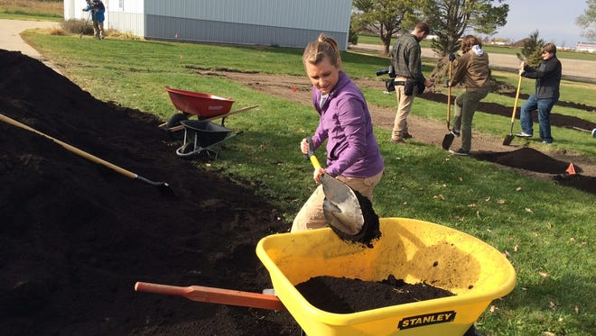 """Devon Leslie, a North Liberty Community Pantry student intern, was one of several volunteers who worked in November 2014 to prepare soil at the site where the pantry planted its """"Growing Together Garden."""""""