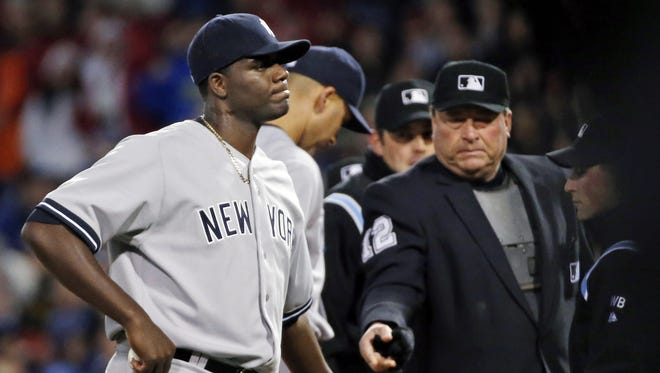 Home plate umpire Gerry Davis ejects New York Yankees starting pitcher Michael Pineda after a foreign substance was discovered on his neck in the second inning of a game against the Boston Red Sox at Fenway Park in Boston.