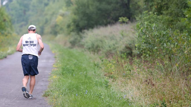 Bill Lawler runs down the Auburn Trail with wife Molly and friend Kathleen Wagner during his twice weekly run Friday, Sept. 9, 2016 in Victor.