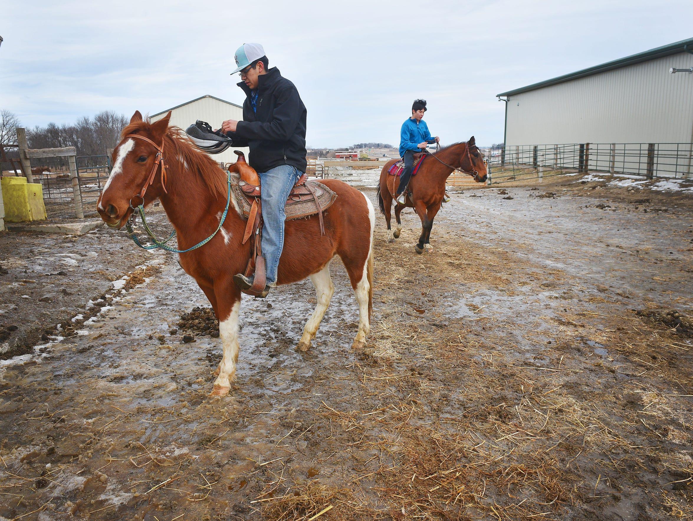 TJ, 16, left, and Omi Schulte, 20, right, ride horses