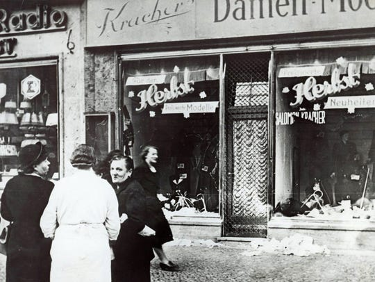 A group of people stand outside a Jewish-owned shop
