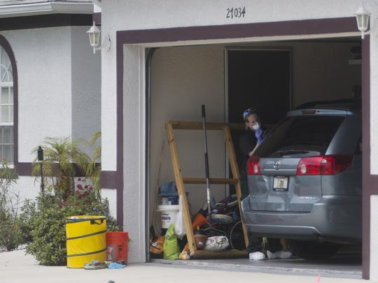 A crime scene technician for the Lee County Sheriff's Office investigates the Bonita Springs home where Dr. Teresa Sievers was found dead.