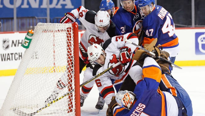 New Jersey Devils' right wing Nick Lappin (36) tries to dig the puck out from beneath New York Islanders' goalie Thomas Greiss (1) as New Jersey Devils left wing Miles Wood (44) resists Islanders' defenseman Travis Hamonic (3) and right wing Colin Markison (47) during the third period of a preseason hockey game Monday night in New York. The Islanders defeated the Devils 4-3.