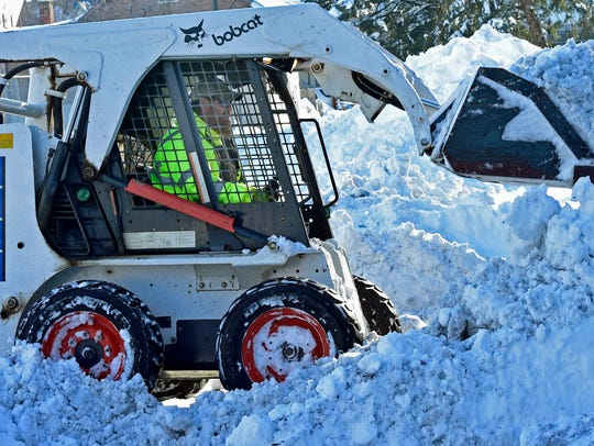 Borough worker Russell Lake uses a Bobcat to plow snow