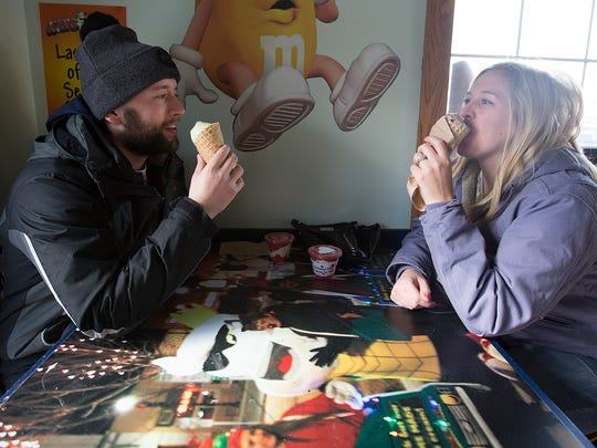 Josh Hames of Plover and his wife Kelsey Hames enjoy their ice cream cones on the opening day of King Kone's season in Plover, Friday, Feb. 12, 2016.