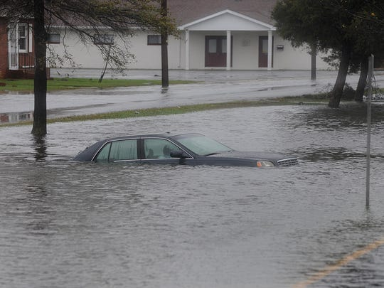A car sits flooded near downtown Crisfield following