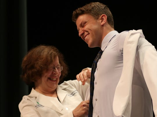 Matthew Novitch is coated during the Medical College of Wisconsin Central Wisconsin White Coat Ceremony at UW Marathon County, in Wausau, Wisconsin, July 7, 2016.