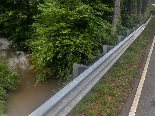 A car drives toward a bridge over Gilder Creek on Holland Road, near Holly Tree Golf course in Greenville. An environmental impact study is made as construction is made to major roads nearby.