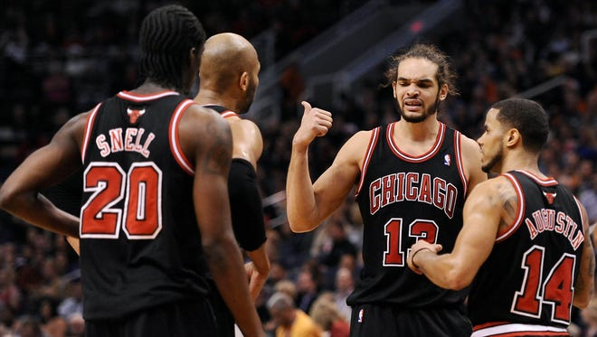 Chicago Bulls center Joakim Noah (13) talks with teammates guard Tony Snell (20), forward Taj Gibson (22) and guard D.J. Augustin (14) on the court against the Phoenix Suns in the first half at US Airways Center