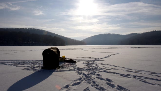 Bill Powers of Yonkers sits in a shelter on the ice as he fishes on the frozen Boyds Corner Reservior in Kent Jan. 19, 2009.  (Stuart Bayer / The Journal News)