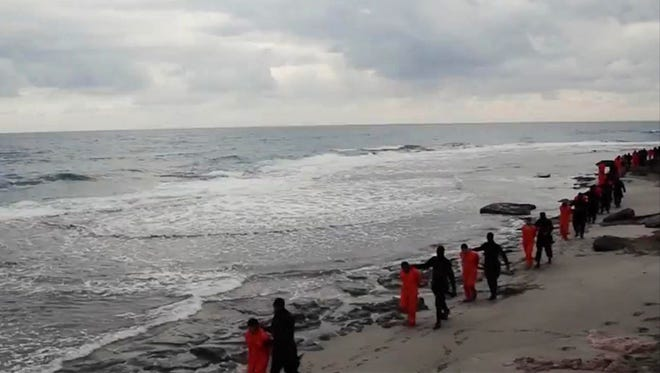 Egyptian Coptic Christians in orange jumpsuits are led along a beach by Islamic State militants in a video released Feb. 15, 2015.