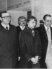 Don Miller is flanked by detectives Dean Tucker, left,