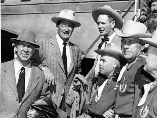"""11/26/1953 PREMIERE STARS ARRIVE IN EL PASO - When Ward Bond and John Wayne (two on left) arrived in El Paso Wednesday for the premiere showing of the much-discussed motion picture, """"Hondo,"""" they were met at International Airport by a delegation which included members of El Paso County Sheriff's Posse. On the right the men are Sheriff W.O. """"Jimmy"""" Hicks; Bill Boling, Fulton Robinson, president of the posse organization, and H. D. Fulwiler."""
