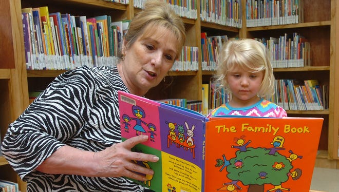 The Krotz Springs library celebrated its expansion in 2014 with an open house. Madyson Girard, right, reads with head librarian Jo Anne Johnson.