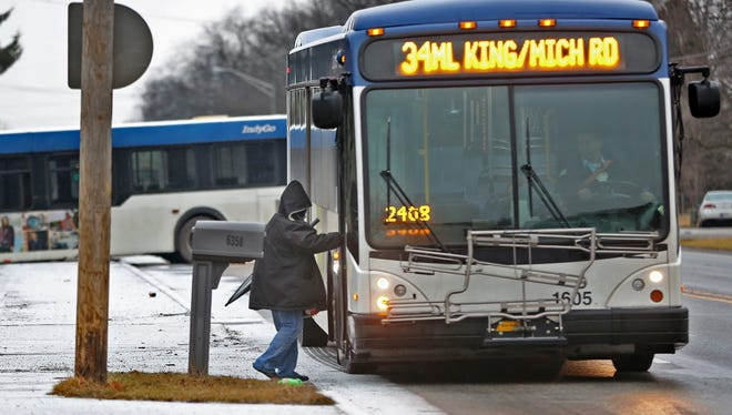 A bus rider gets on a bus near where another IndyGo bus had slid off in the 6400 block of Michigan Rd., Wednesday, Jan. 24, 2018.  Ice caused countless slide offs and accidents for the morning commute.  Several school systems closed also as a result of the icy weather.