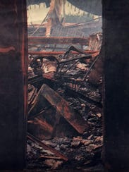 A view through a door shows the charred remains of