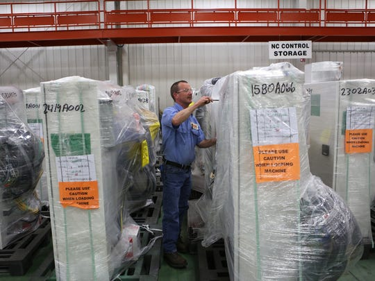 Mike Quatman of Sunman, Indiana, who works for Mazak Corporation, unwraps part of a machine.