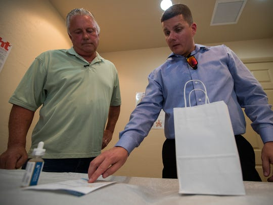 Allen Bills, left, a medical marijuana patient, discusses the details of his medication order with Matthew Lipani, an assistant manager with Surterra Inc., Thursday, March 1, 2018. Surterra, a medical marijuana distributor, provides delivery services to patients unable to visit their store locations.