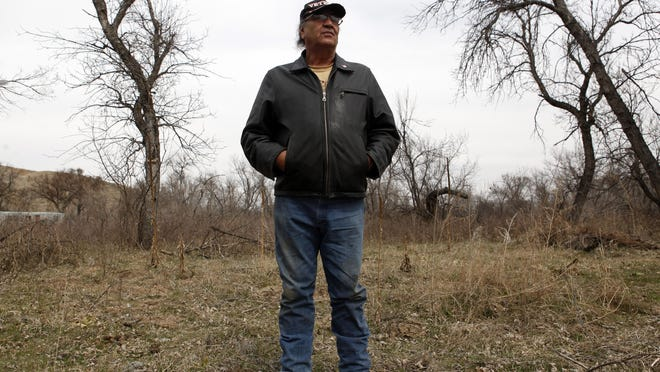 Alex White Plume stands in the field Tuesday, March 29, 2016, where he once cultivated hemp near his home on the Pine Ridge Reservation near Manderson, S.D. White Plume's crop was chopped down by DEA agents more than a decade ago. Now an injunction has been lifted by the court and White Plume can start exploring hemp cultivation again. Chris Huber photo