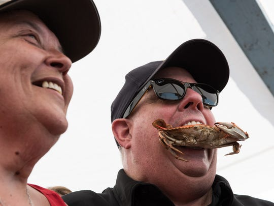 Kim East, of Crisfield, poses for a photo with Governor Larry Hogan while he jokingly puts a crab in his mouth during the 2016 J. Millard Tawes Crab & Clam Bake in Crisfield.