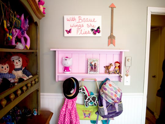 """Toys and other belongings on a wall in Emma's bedroom. Emma likes pink things, Hello Kitty, and Jessie the yodeling cowgirl from """"Toy Story II."""""""