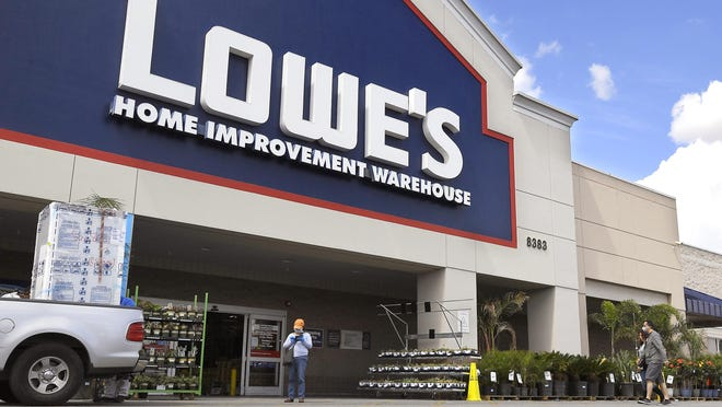 In this March 22 photo, customers wearing masks walk into a Lowe's home improvement store in the Canoga Park section of Los Angeles.