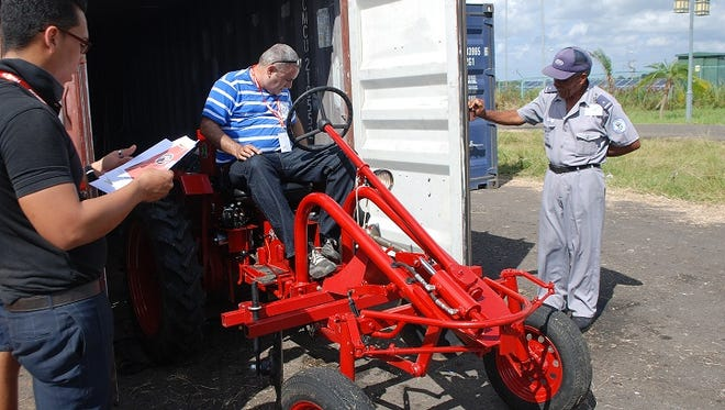 "Cuban officials unload an American-made tractor at the Port of Mariel on Oct. 23, 2015. The ""Oggún"" was built by Alabama-based Cleber LLC, which will display the tractor at the International Trade Fair in Havana in hopes of selling them to Cuban farmers."