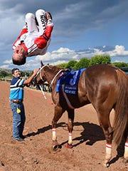 Jockey G.R. Carter, Jr.'s trademark back flip dismount.