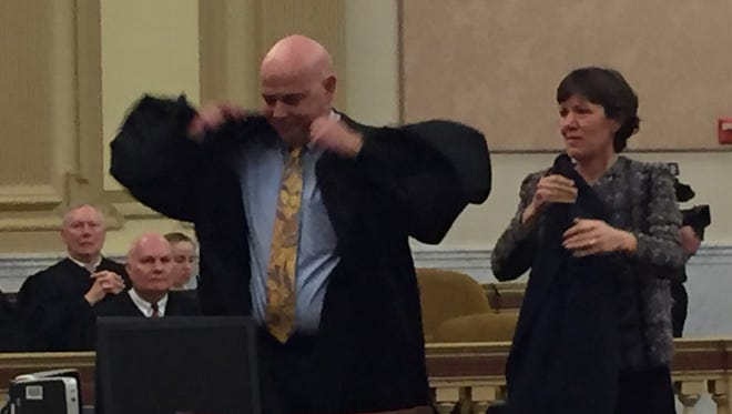 Mike Flannelly, who was elected York County Court of Common Pleas Judge, puts on his robe with the help of his wife, Peggy.