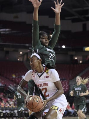 Maryland Shatori Walker-Kimbrough, front, shoots as Wagner center Ugo Nwaigwe defends during the first half of an NCAA college basketball game Sunday, Nov. 16, 2014 in College Park, Md. Maryland won 97-24.