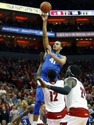 Kentucky's Trey Lyles (#41) floats a shot over Louisville's Mangok Mathiang (#12) and Montreal Harrell. Dec. 27, 2014.