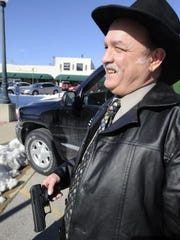 Baxter County Judge Mickey Pendergrass shows his 9mm Hi-Point semi-automatic handgun. Pendergrass carries the weapon with him in his county vehicle while working. Pendergrass said he would have no problem if other county employees carried guns with them in county vehicles as long as they had the proper permits.