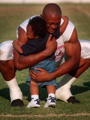 In this 1998 photo, then-Oilers running back Eddie George hugs son Jaire, then 16 months old. after practice. Jaire, now a high school senior, has committed to Vanderbilt.