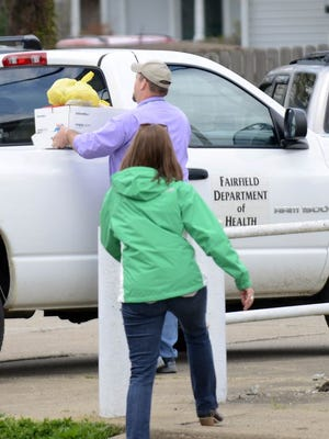 A man carries a box of food from the Cross Pointe Free Will Baptist Church Family Life Center to a Fairfield County Health Department truck Wednesday, April 22, 2015, in Lancaster. One person is dead and more than a dozen people are in area hospitals after a suspected outbreak of botulism that officials believe is tied to a lunch Sunday at the church.