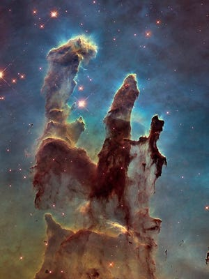 """This image made by the NASA/ESA Hubble Space Telescope shows the Eagle Nebula's """"Pillars of Creation."""" The dust and gas in the pillars is seared by the intense radiation from young stars and eroded by strong winds from massive nearby stars. The Hubble Space Telescope marks its 25th anniversary."""