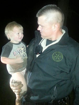 Allegan County Deputy Ben Haas holds the boy found after disappearing for several hours.
