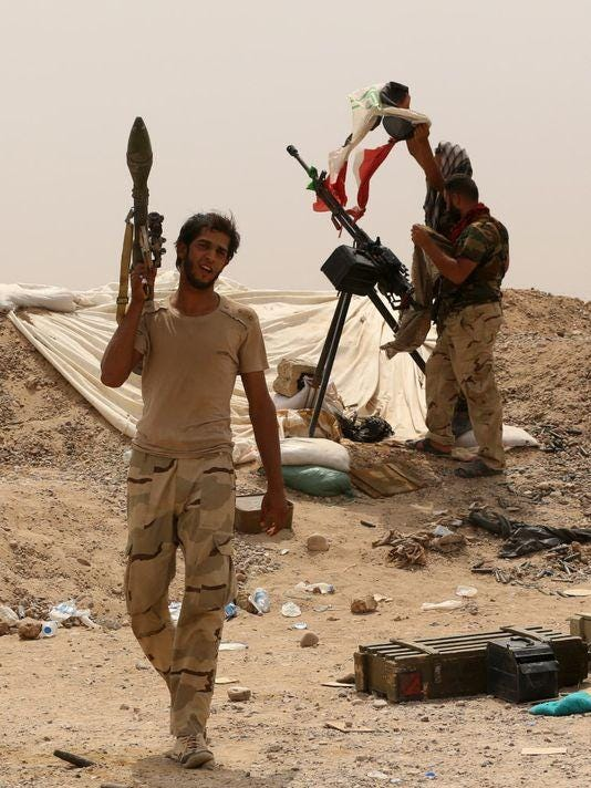 Fighters from a Shiite militia stand guard at the front line in Anbar provin