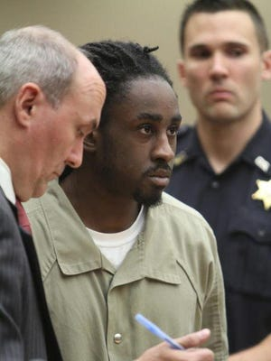 Michael Caruthers, center, being arraigned in court on rape charges in September 2014.