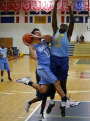 Danny Brix (11) of the NJ Tar Heels drives to the basket against Willie Irick (23) during Jersey Shore Basketball League game at Wall Township High School.