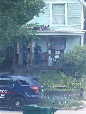 Viral photo of Grand Rapids police searching for man hiding on the roof by Richdakilla.