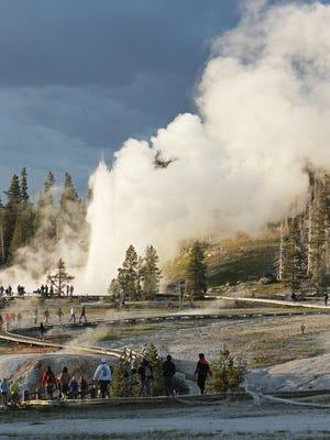 Visitors on a boardwalk observe the Grand Geyser in Upper Geyser Basin of Yellowstone National Park.